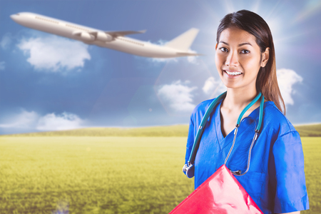 success asian: Asian nurse with stethoscope looking at the camera against sunny green landscape Stock Photo