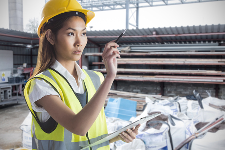 yellow helmet: Architect woman with yellow helmet and plans against building site Stock Photo