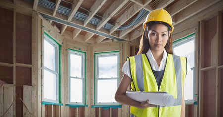 house under construction: Architect woman with yellow helmet and plans against house under construction