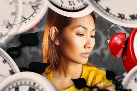 ticking away: Serious asian woman looking down against black background