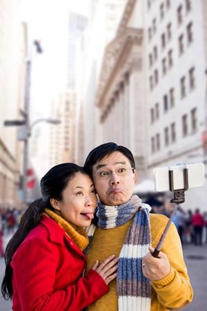 ear muff: Older asian couple on balcony taking selfie against new york street Stock Photo
