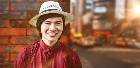 a house with a straw: Smiling hipster with a straw hat against wall of a house