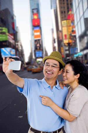 high def: Man and woman taking a picture against picture of a city Stock Photo