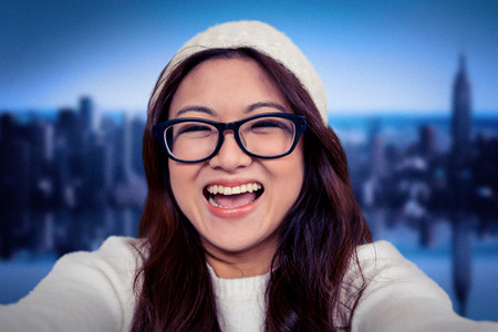 mirror image: Asian woman smiling at the camera against mirror image of city skyline Stock Photo