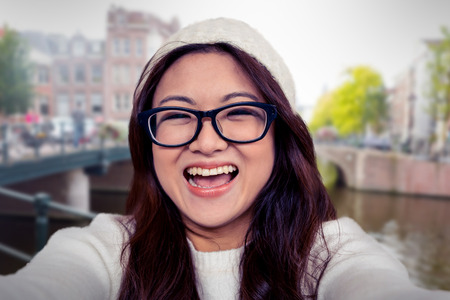 Asian woman smiling at the camera against canal in amsterdam Banco de Imagens