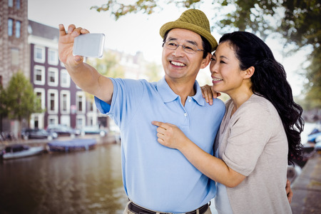 high def: Man and woman taking a picture against canal in amsterdam