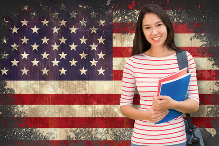 people relax: College girl holding books with blurred students in park against usa flag in grunge effect