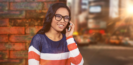 Asian woman on a phone call against wall of a house Stock Photo
