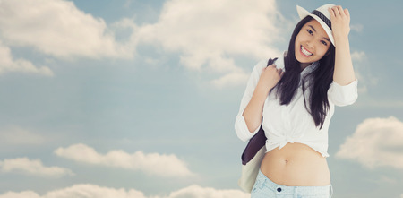 beautiful navel women: Woman with casual clothes holding her hat against beautiful blue cloudy sky Stock Photo