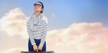 Asian woman with luggage looking up against beautiful blue cloudy sky