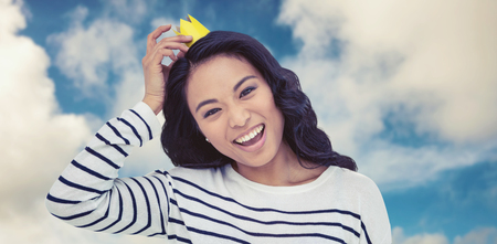 pre adult: Smiling Asian woman with paper crown against road leading out to the horizon