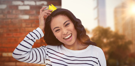pre adult: Smiling Asian woman with paper crown against wall of a house
