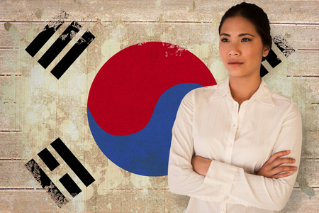 Casual businesswoman with arms crossed against korea republic flag in grunge effect