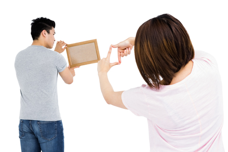 putting up: Young couple putting up picture frame on white background