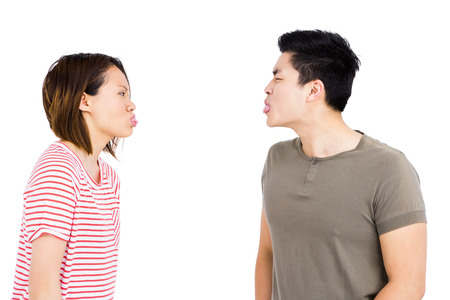 teasing: Young couple teasing each other on white background