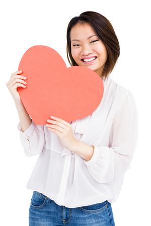 heart symbol: Portrait of woman holding heart shape on white background