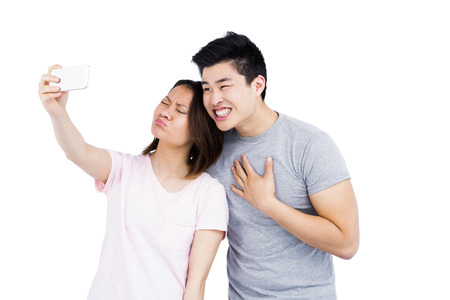 in loving memory: Young couple taking a selfie on smartphone on white background