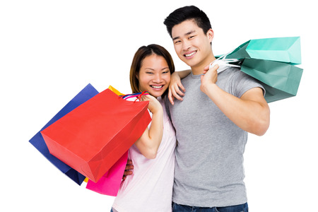 Portrait of young couple with shopping bags on white background Stock Photo