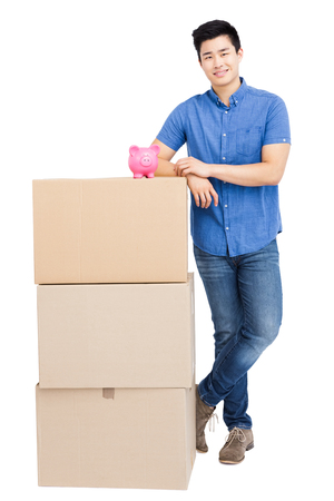 Young man standing near cardboard boxes with piggy bank on white background