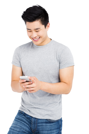 Young man text messaging on mobile phone on white background Imagens