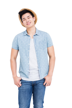 hands on pocket: Young man standing with hands in pocket and smiling on white background