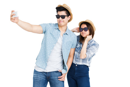 cut out device: Happy young couple taking a selfie on white background