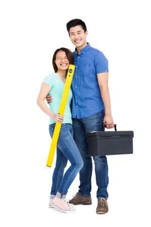 spirit level: Young couple standing with spirit level measuring tool and tool box on white background