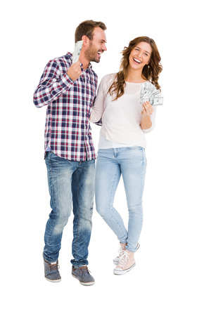 fanned: Happy young couple holding fanned out currency notes on white background