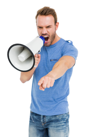 angry person: Young man shouting on horn loudspeaker on white background Stock Photo