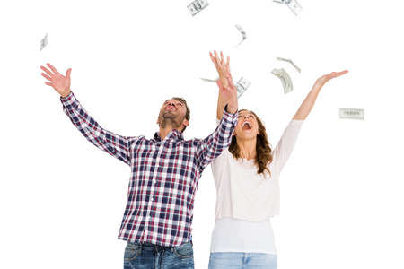 mid adult women: Happy young couple throwing currency notes in air on white background