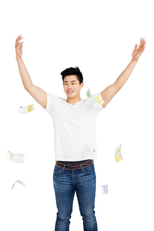Happy young man throwing currency note on white background Stock Photo