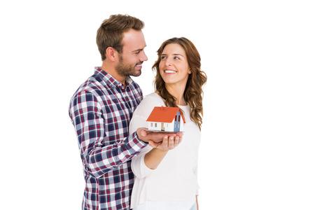 model house: Happy young couple holding model house on white background Stock Photo