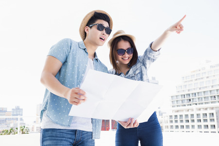 Happy young couple using map for direction outdoors