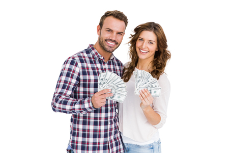 fanned: Portrait of happy young couple holding fanned out currency notes on white background Stock Photo