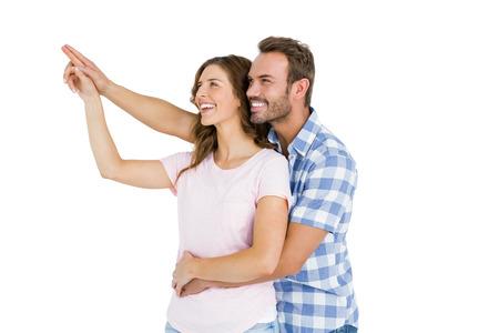 upward: Happy young couple embracing and pointing upward on white background