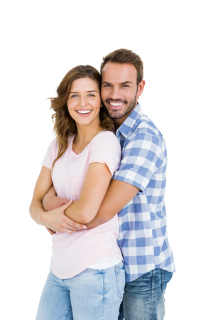 Portrait of happy young couple embracing on white background