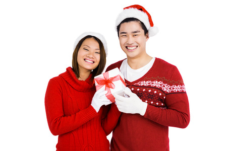 attire: Portrait of young couple in christmas attire holding gift on white background