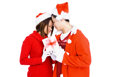attire: Young couple in christmas attire holding gift on white background