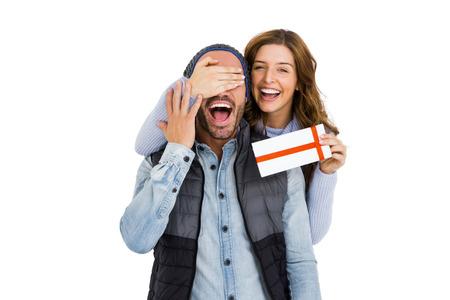 Cubierta de la mujer sirve ojos mientras le da un regalo sorpresa en el fondo blanco Foto de archivo - 53949527