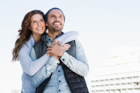 each other: Happy couple embracing each other and smiling outdoors
