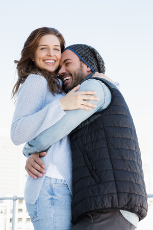 each: Happy couple cuddling each other and smiling outdoors