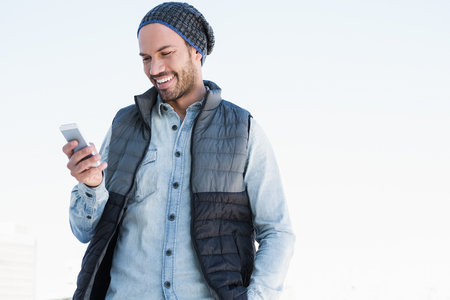 Happy young man text messaging on mobile phone
