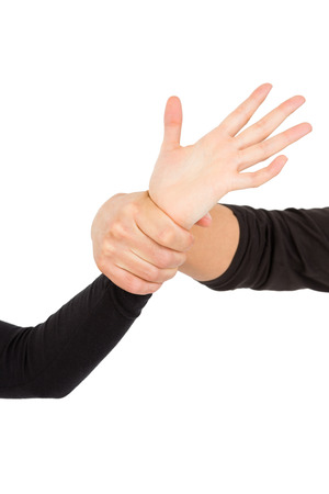 female domination: Close-up of hand holding wrist on white background