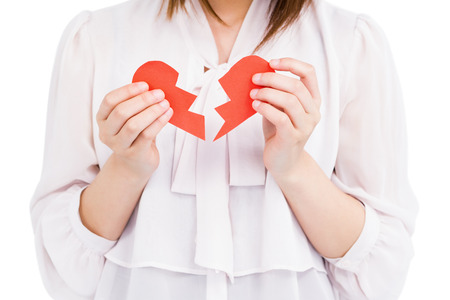heartbreak issues: Young woman holding broken heart on white background
