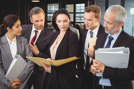 ejecutiva en oficina: Abogado mirando a los documentos e interactuar con los hombres de negocios en la oficina