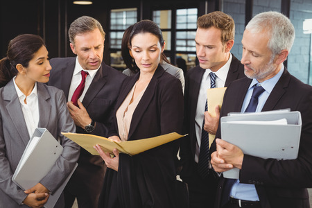 female lawyer: Lawyer looking at documents and interacting with businesspeople in office