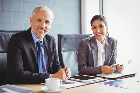 team leadership: Portrait of businessman and businesswoman sitting in conference room Stock Photo