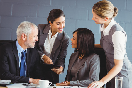 interacting: Businesspeople interacting in conference room in office Stock Photo