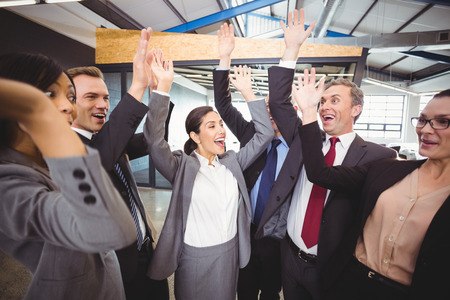 raising hands: Cheerful businesspeople raising hands in office
