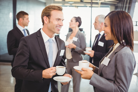 interacting: Businesspeople having tea and interacting during break time in office Stock Photo